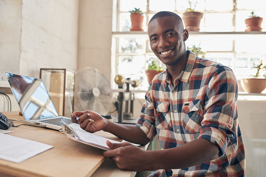 Business Insurance - Portrait Of Young Small Business Owner Sitting In His Office