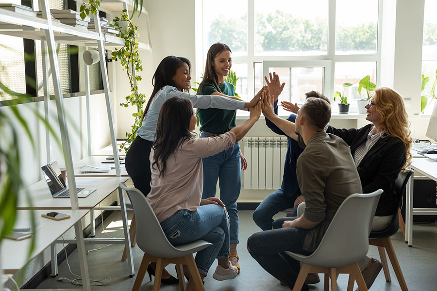 Employee Benefits - Group Of Employees Sitting In Office Giving Eachother High Fives